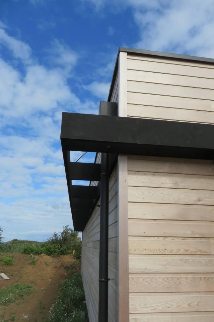 Maison bois Finistère bandeau en Noir de Falun dissimule les coffres de volets roulants